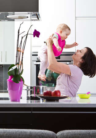 Young mother playing with her baby daughter in a modern kitchen setting. photo