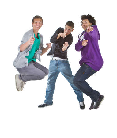 Three multiracial teenagers jumping over joy over white background. Stock Photo