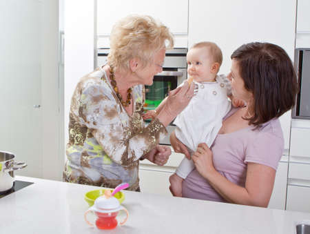 Young mother with baby girl and the grandmother in a modern kitchen setting. photo
