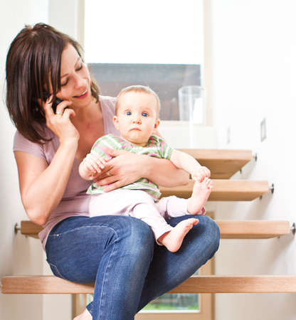 Young mother sitting with her baby on stairs while talking on the cellphone. photo