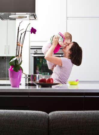 convivencia familiar: Joven madre jugando con su hija en un entorno de cocina moderna.