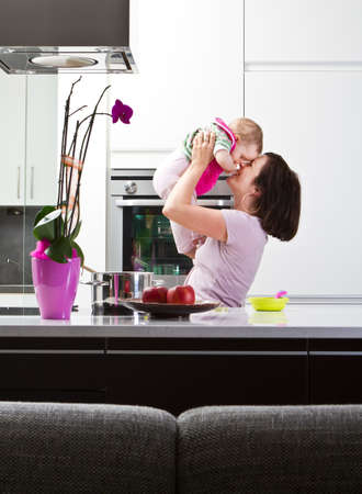 Young mother playing with her baby daughter in a modern kitchen setting. Stock Photo - 9471169