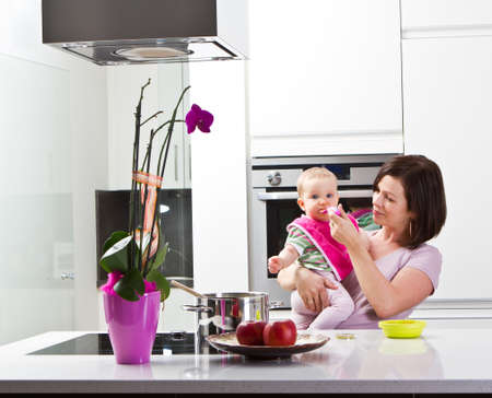 Young mother is feeding her baby in a modern kitchen setting. photo