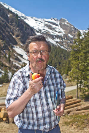 Senior man hiking in beautiful nature surrounding with big mountains in the back. photo