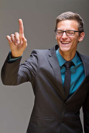 Young business man pushing digital buttons. Cool man with glasses. photo