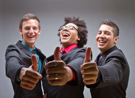 Three young multiracial business man show a thumb up sign and express positveness. photo