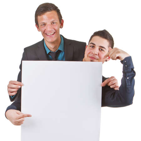 Two young business men presenting a white sign with copyspace. Stock Photo - 9663431