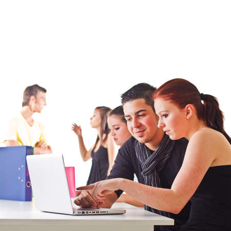 Young couple in front of laptop with others in the background. Candid picture. Stock Photo - 10159776