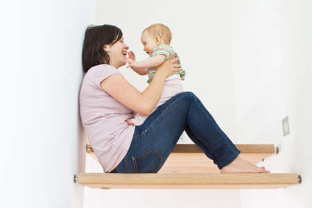 Young mother at home with her little baby on stairs. photo
