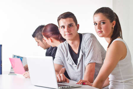 Young couple in front of laptop with others in the background. Candid picture. Stock Photo - 10078267