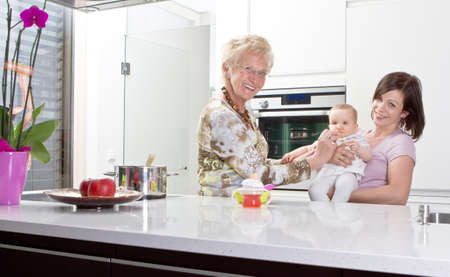 Young mother with baby girl and the grandmother in a modern kitchen setting. Stock Photo