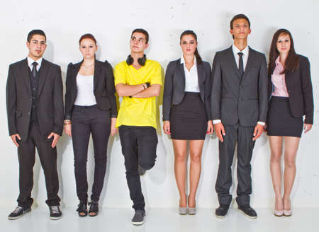 standout: Young group of teenage business people with one young man standing out of the crowd.