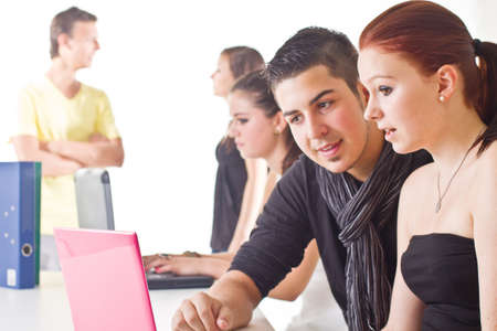 six girls: Young couple in front of laptop with others in the background. Candid picture.