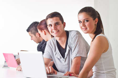 Young couple in front of laptop with others in the background. Candid picture.