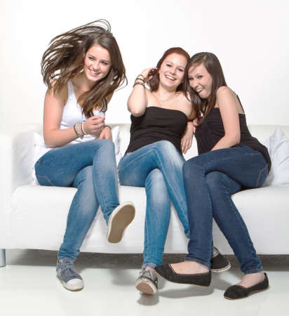 teen girl bedroom: Three young beautiful women sitting on a couch enjoying a talk. Stock Photo