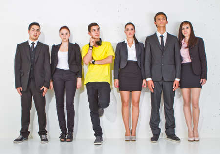 Young group of teenage business people with one young man standing out of the crowd. photo