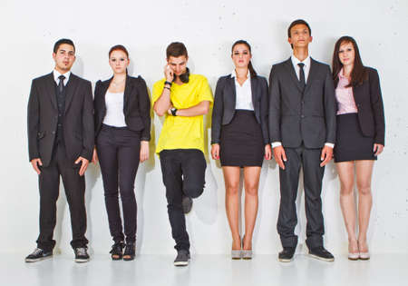 Young group of teenage business people with one young man standing out of the crowd.