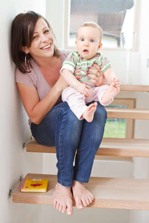 young girl barefoot: Young mother at home with her little baby on stairs.