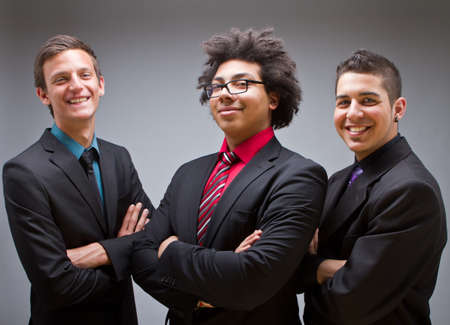 teenage male: Three young businessman posing at the camera. Trendy and Cool.