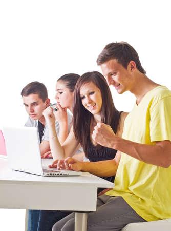 Joven pareja delante del ordenador portátil con otros en el fondo. Imagen de Franco. Foto de archivo