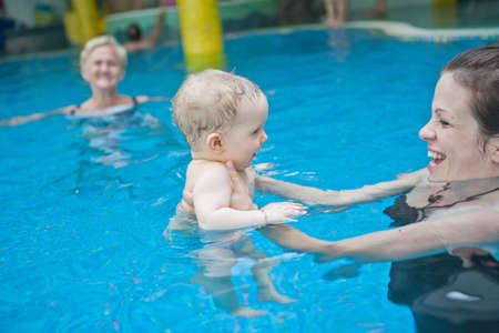 Young family with baby having fun in the swimming pool. Stock Photo