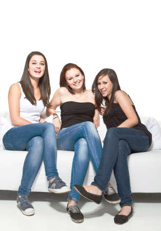 Three young beautiful women sitting on a couch enjoying a talk. photo
