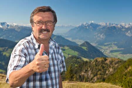Senior man on top of a mountain Stock Photo
