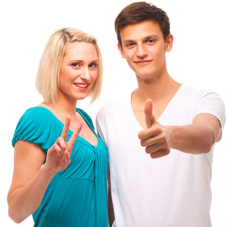 Young couple isolated over white showing thumbs up sign. photo