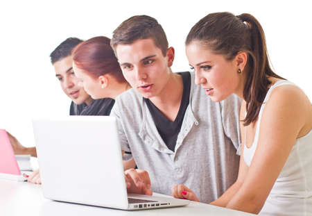 Young couple in front of laptop with others in the background. Candid picture. photo