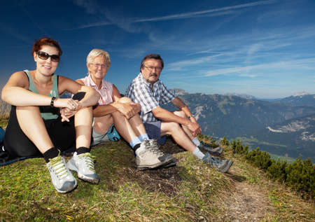 Two older parents with their daughter on top of a mountain photo
