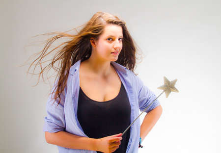 Young woman with a magic wand over grey background. photo