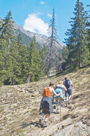 Family with senior parents and a young daughter hiking in the mountains photo