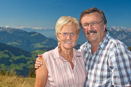 Senior couple hiking in the mountains over blue sky photo