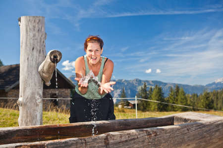 Young woman drinking and playing with water in the alps. photo