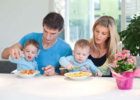 Young family having a hard time feeding baby twins photo