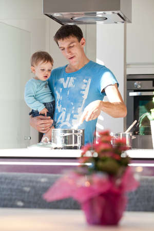 single father: Young father cooking with his baby son in a modern kitchen.