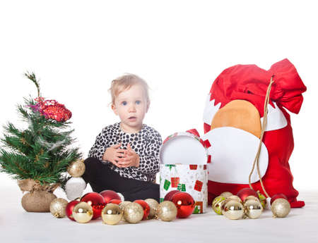 Young baby girl in a christmas setting isolated over white background. photo