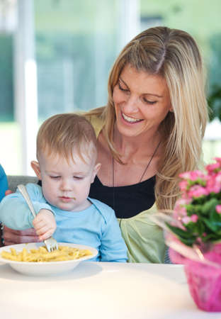 Young modern mother ist feeding her little son with noodles. photo