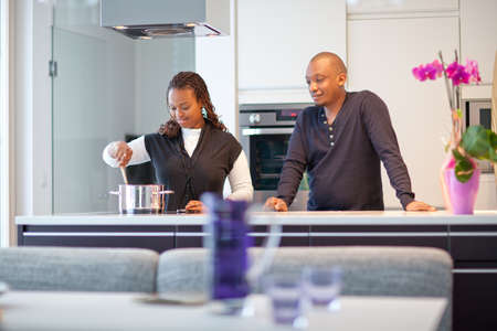 Colored couple in a modern kitchen setting. The woman is cooking.