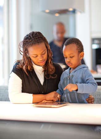 Kitchen setting with young black family playing with a tablet pc. Stock Photo - 12116417