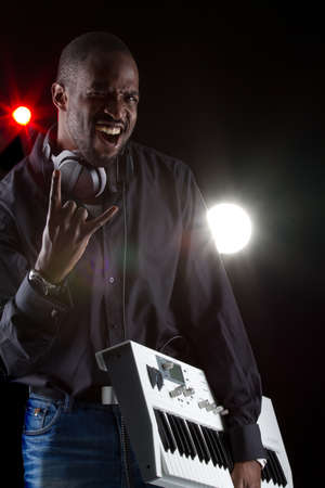 Young black man with a keyboard and headphones over black background. photo