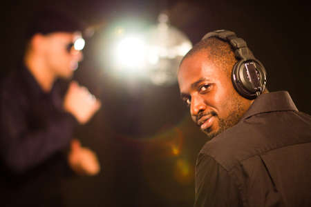Black young dj working over black background. Stock Photo