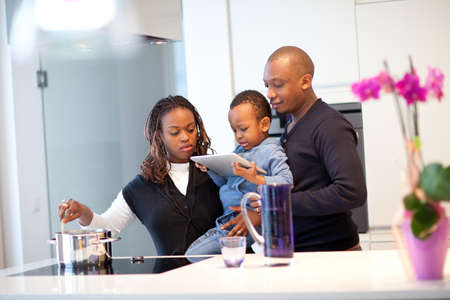 black family: Kitchen setting with young black family playing with a tablet pc.