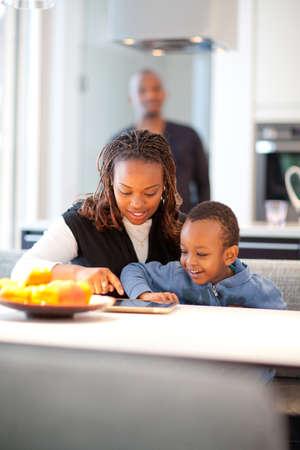pepe nero: Ambiente cucina con la giovane famiglia nera che gioca con un tablet pc.