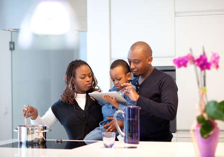 wives: Kitchen setting with young black family playing with a tablet pc.