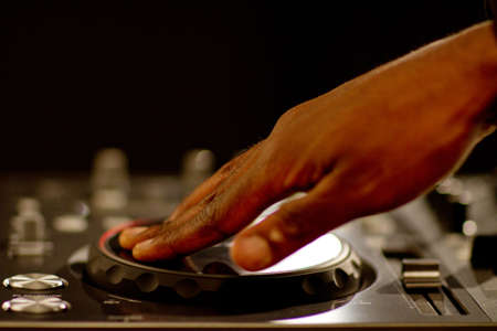 dj turntable: Hands of a black dj on turntables during a party. Stock Photo