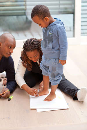Young black family sitting on the floor drawing a picture with their son. Stock Photo - 12654634