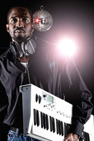 keyboard instrument: Young black man with a keyboard and headphones over black background. Stock Photo