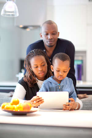Kitchen setting with young black family playing with a tablet pc. photo
