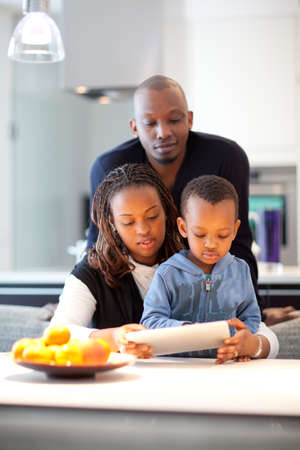 Kitchen setting with young black family playing with a tablet pc. Stock Photo - 12922173